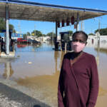 Andrienne Dolley stands in front of a gas station surrounded by floodwaters