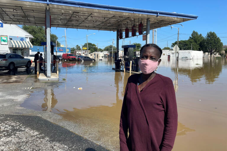 Andrienne Dolley stands in front of a gas station whose lot was left submerged by Ida's remnants. (Cris Barrish/WHYY)