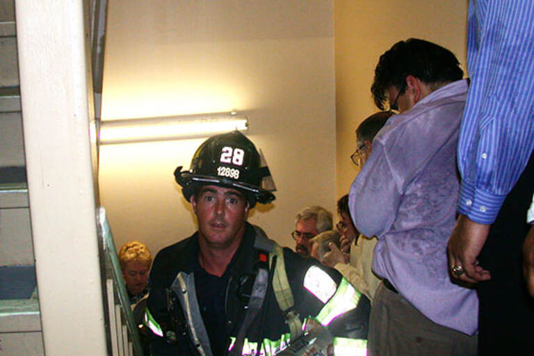 Firefighter Mike Kehoe rushes up the stairs of the North Tower as office workers including John Labriola, who took this photo, file down the stairs on Sept. 11, 2001. Both Kehoe and Labriola survived the attacks. (AP Photo/John Labriola)