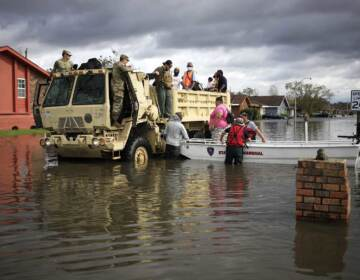 First responders drive a high water vehicle through flooded streets while rescuing residents