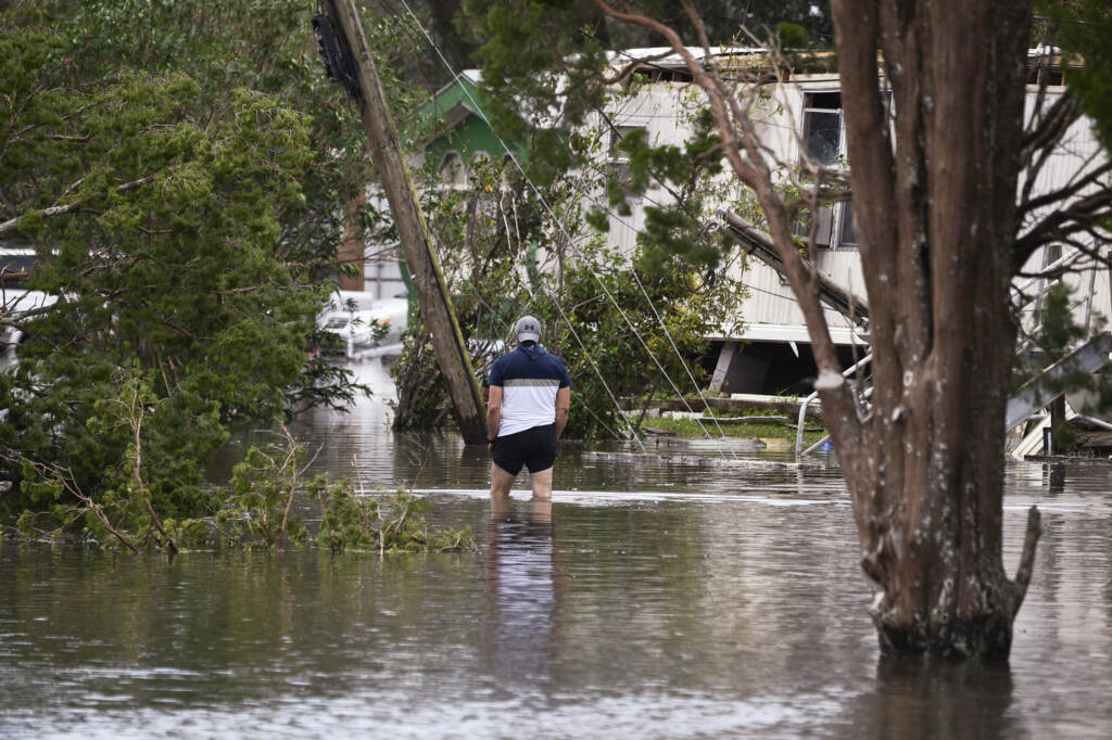 A person wades through flood waters in Norc