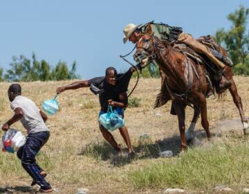 A U.S. Border Patrol agent on horseback tries to stop a Haitian migrant from entering an encampment on the banks of the Rio Grande