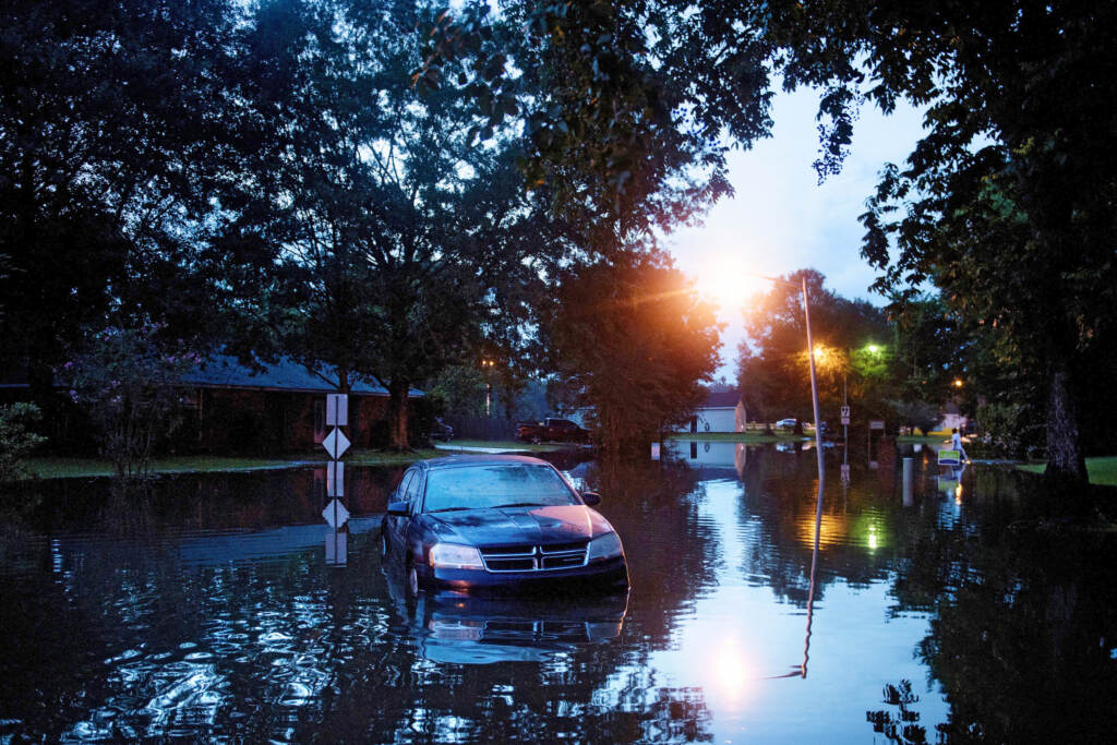 An abandoned car is seen in a flooded street