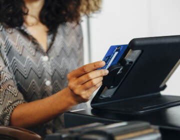 A cashier swipes a credit card at a register.