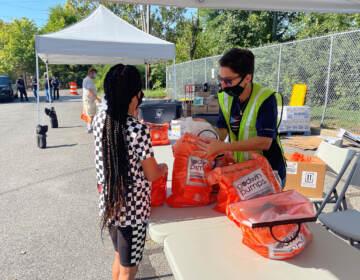 A volunteer hangs a bag of snacks to Kia Bell