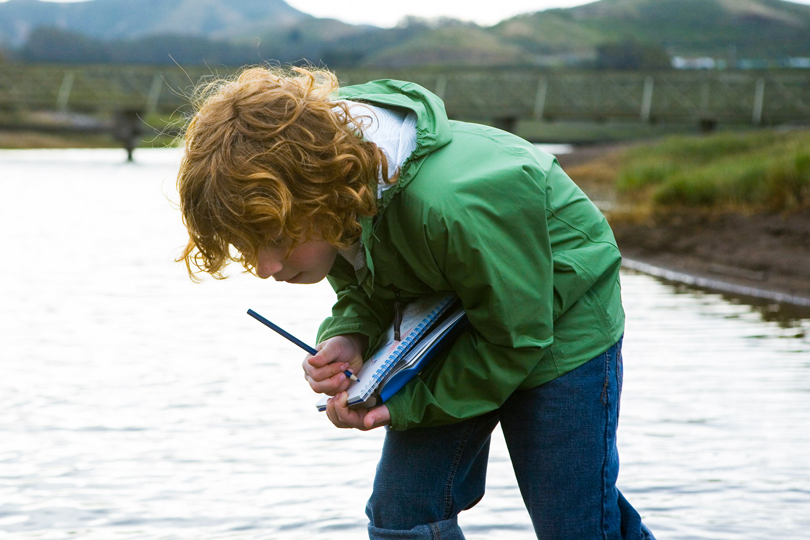 A young boy observing nature and writing things down in a notebook