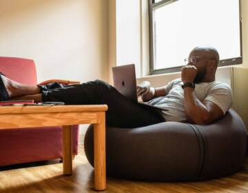 A man sitting on a bean bag chair working from home