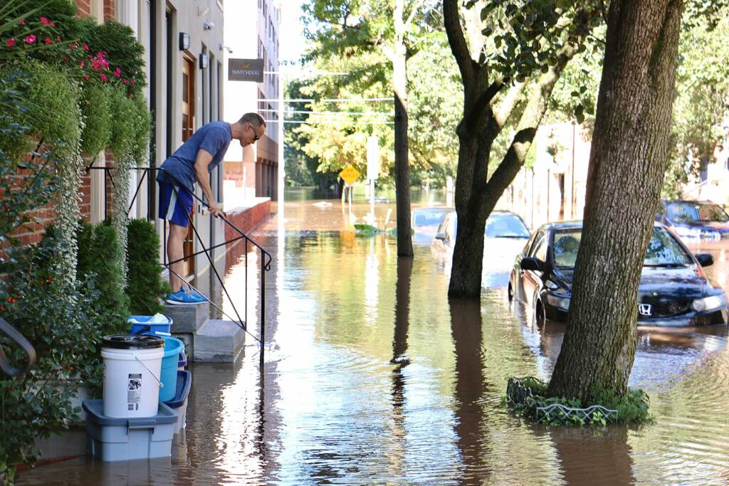 A person stands on their stoop, surrounded by rising floodwater