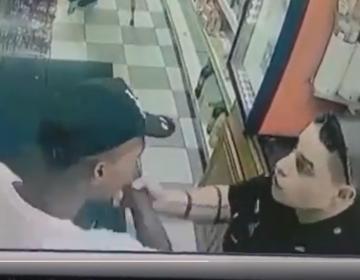 Patrolman Samuel Walters (right) grabs Dwayne Brown's arm moments into their encounter.  (Courtesy of Ivan Thomas/DETV)