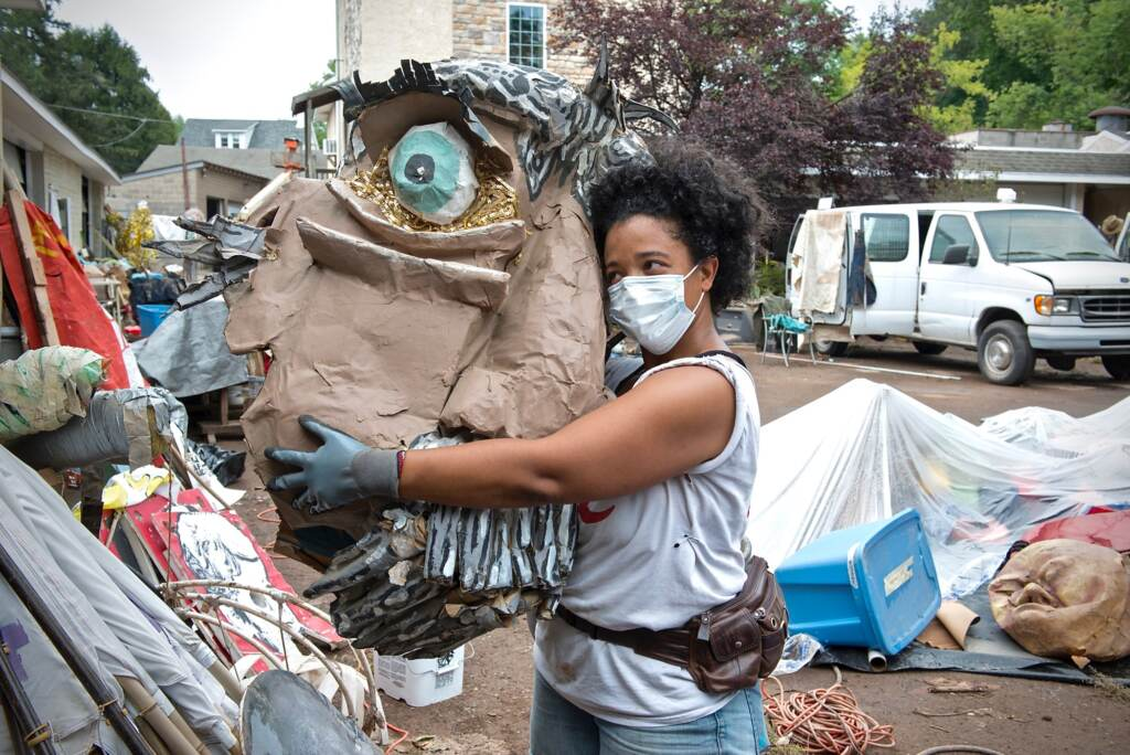 Co-artistic director Jennifer Turnbull hugs a puppet head that was made with addiction recovery residents at Girard Medical Center, as part of its arts therapy program. It survived the flood