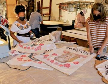 Spiral Q co-directors Jennifer Turnbull (left) and Liza Goodell work on memorial banners to be carried in the Philly Trans Parade. The banners survived the flood at Spiral Q's storage facility in Mont Clare, Pa