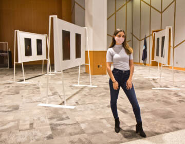 Katherine Cambareri, a graduate with a masters degree in public health from Jefferson College of Population Health, stands with her photographs of clothes worn by survivors of sexual violence at her exhibit at Eakins Lounge at Jefferson Alumni Hall on October 6, 2021. (Kimberly Paynter/WHYY)