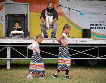 Kai'Lyn Ellis, 5, and her sister, Li'Ana Ellis, 10, members of the Nanticoke Lenape tribe, perform a toe dance while their father, Tyron Ellis chants at Philadelphia's Indigenous Peoples Day celebration at Penn Treaty Park. (Emma Lee/WHYY)
