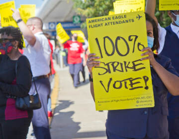 Workers hold up yellow signs at a protest outside PHL Airport