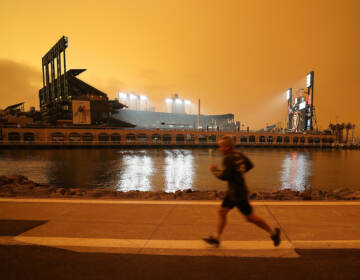 A jogger runs along McCovey Cove outside Oracle Park, under darkened skies from wildfire smoke