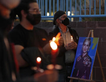 Mourners, wearing face masks, are pictured holding candles at a vigil for Halyna Hutchins