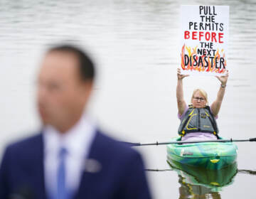 Libby Madarasz displays a protest placard against a pipeline