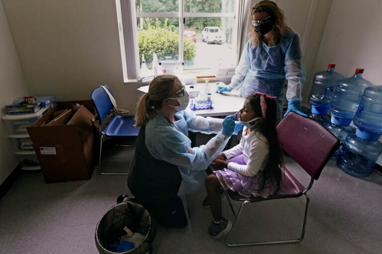 School nurse Denise Corrigan, left, tests a student for COVID-19 at the E.N. White School in Holyoke, Mass., on Wednesday, Aug. 4, 2021. (AP Photo/Charles Krupa)