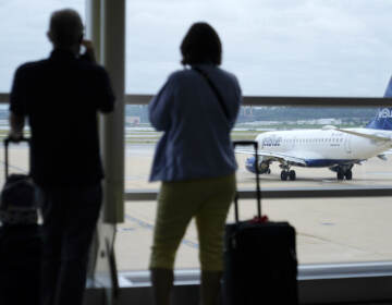 Travelers watch a JetBlue Airways aircraft taxi away from a gate at Ronald Reagan Washington National Airport†ahead of Memorial Day weekend, Tuesday, May 25, 2021, in Arlington, Va