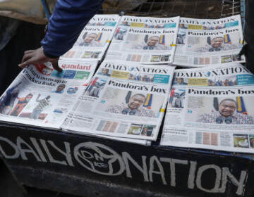 Kenyans read the morning newspapers reporting a statement issued by President Uhuru Kenyatta following reports that he is among more than 330 current and former politicians identified as beneficiaries of secret financial accounts, in the low-income Kibera neighborhood of Nairobi, Kenya Tuesday, Oct. 5, 2021
