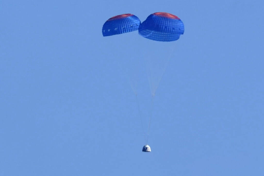 Parachutes carry the Blue Origin's capsule with passengers William Shatner, Chris Boshuizen, Audrey Powers and Glen de Vries from its spaceport near Van Horn, Texas, Wednesday, Oct. 13, 2021