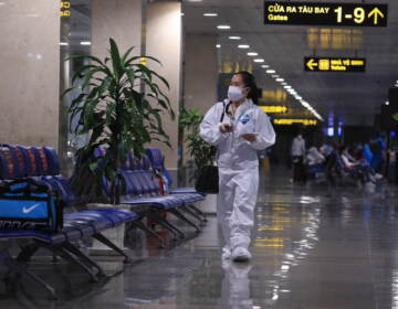 A passenger in full protective suit walks to boarding gate at Tan Son Nhat airport in Ho Chi Minh city, Vietnam on 15 Oct. 2021. Vietnam has resumed air travel after several months of suspension due to COVID-19 outbreak