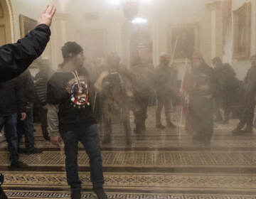In this Jan. 6, 2021, file photo, smoke fills the walkway outside the Senate Chamber as supporters of President Donald Trump, including Eric Bochene, far right, are confronted by U.S. Capitol Police officers inside the Capitol in Washington. (AP Photo/Manuel Balce Ceneta, File)
