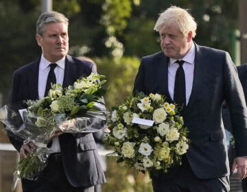 British Prime Minister Boris Johnson, right, and Leader of the Labour Party Keir Starmer carry flowers as they arrive at the scene where a member of Parliament was stabbed Friday, in Leigh-on-Sea, Essex, England, Saturday, Oct. 16, 2021