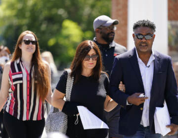 File photo: Former NFL players Ken Jenkins, right, and Clarence Vaughn III, center right, along with their wives, Amy Lewis, center, and Brooke Vaughn, left, carrie tens of thousands of petitions demanding equal treatment for everyone involved in the settlement of concussion claims against the NFL, to the federal courthouse in Philadelphia, Friday, May 14, 2021