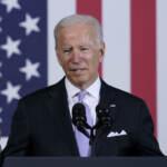 President Joe Biden speaks in front of an American flag backdrop