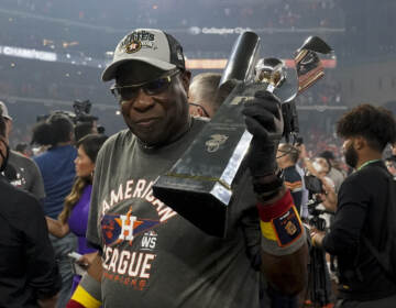 Houston Astros manager Dusty Baker Jr. holds the trophy after their win against the Boston Red Sox in Game 6 of baseball's American League Championship Series Friday, Oct. 22, 2021, in Houston. The Astros won 5-0, to win the ALCS series in game six. (AP Photo/Tony Gutierrez)