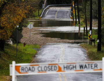 A barricade blocks access to a road flooded by recent rain in Branchburg, N.J., Tuesday, Oct. 26, 2021