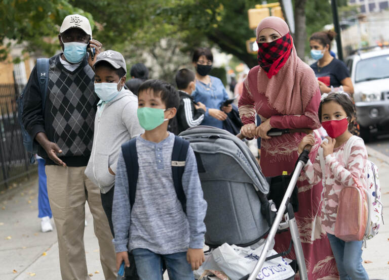 Parents stand with their kids outside, all while wearing face masks