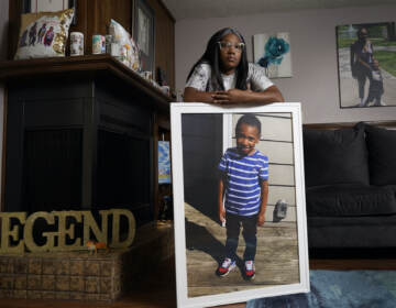 Charron Powell stands with a photo of her son, LeGend Talieferro, at her home