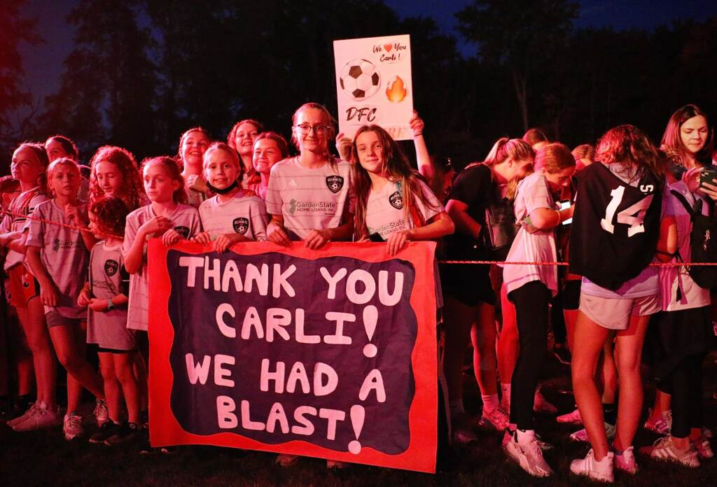 Members of the Delran Football Club carry a banner for Carli Lloyd in the glow from a video monitor