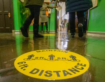 A marker on the floor of a school hallway reminds students to physically distance.