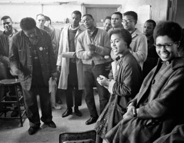 James Forman leads singing in the SNCC office on Raymond Street in Atlanta, (from left) Mike Sayer, MacArthur Cotton, Forman, Marion Barry, Lester McKinney, Mike Thelwell, Lawrence Guyot, Judy Richardson, John Lewis, Jean Wheeler, and Julian Bond, 1963, Danny Lyon