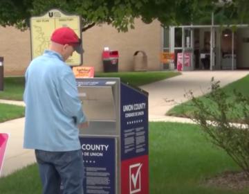 A voter drops their mail ballot through a drop box.