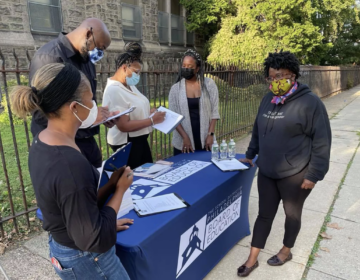 Philadelphia school board member Lisa Salley, right, works with district volunteers in front of Overbrook Elementary School on Thursday to get input from parents in the search for a new superintendent. Standing from left, Kristyn Aldrich, Walter Dixon, Marcia Hall and Deanna Scott. (Johann Calhoun / Chalkbeat)