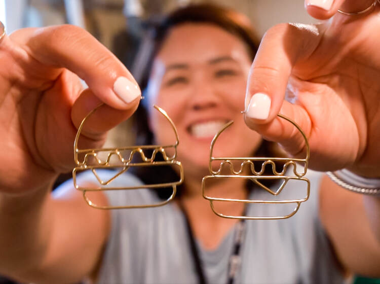Shirley Minn holding a pair of hamburger earrings from Anethum Jewelry