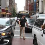 A pedestrian threads his way through snarled traffic
