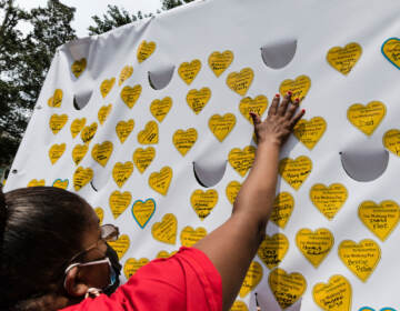 A person places a sticker representing a lost relative on a tribuet wall