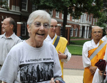FILE - In this Aug. 9, 2012, file photo, Sister Megan Rice, center, and Michael Walli, in the background waving, are greeted by supporters as they arrive for a federal court appearance in Knoxville, Tenn., after being charged with sabotaging a government nuclear complex. Rice, who served two years in prison and was released when her original conviction was thrown out by a federal appeals court, died of congestive heart failure Oct. 10, 2021, at Holy Child Center in Rosemont, Pa. She was 91. (Michael Patrick/Knoxville News Sentinel via AP, File)