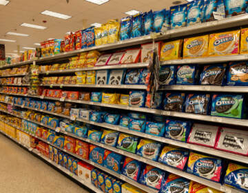 The cookie aisle in a grocery store with two people shopping.