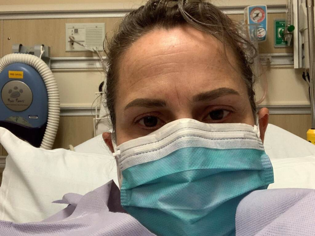 Chelsea Titus is pictured wearing a mask in a hospital bed.
