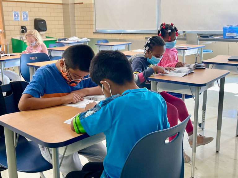 Kids sit at their desks in school