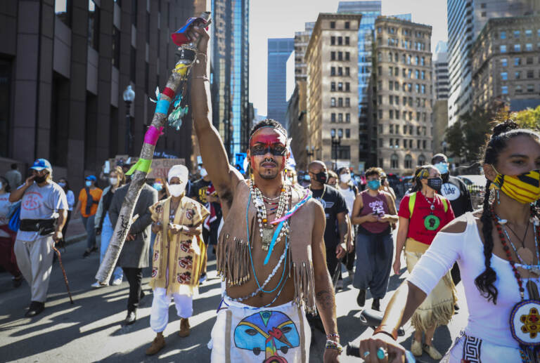 A demonstrator marches to Faneuil Hall with other protesters while participating in the Indigenous Peoples Day rally and march in Boston on Oct. 10, 2020. (Photo by Erin Clark/The Boston Globe via Getty Images)