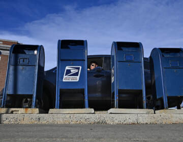 A man pulls up to drop off mail at the mailboxes at the Portland Post Office