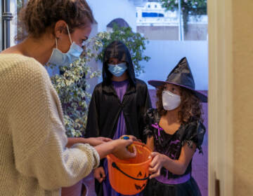 Children dressed in halloween costumes, while wearing face masks, trick-or-treating