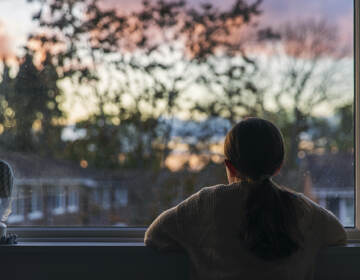 A girl looks out of her bedroom window as the sun is setting